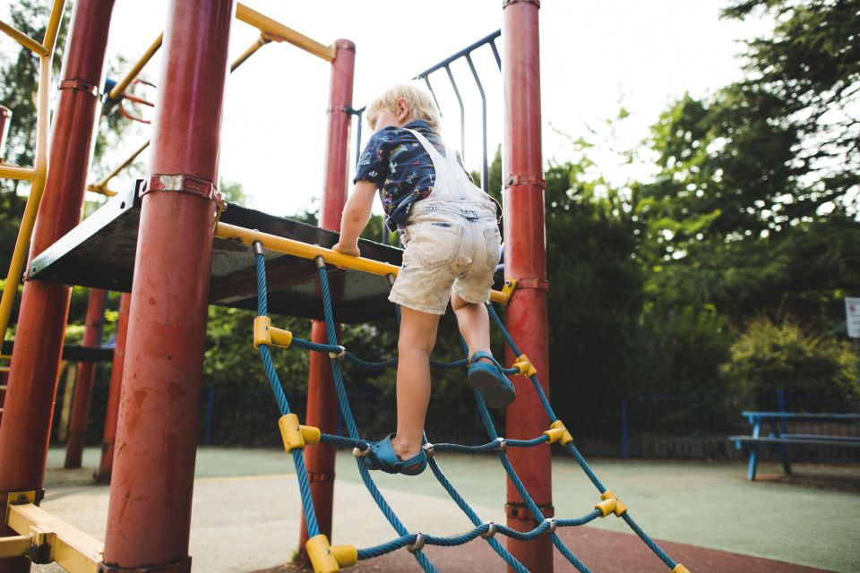 Boy in overalls Climbing up a playground structure