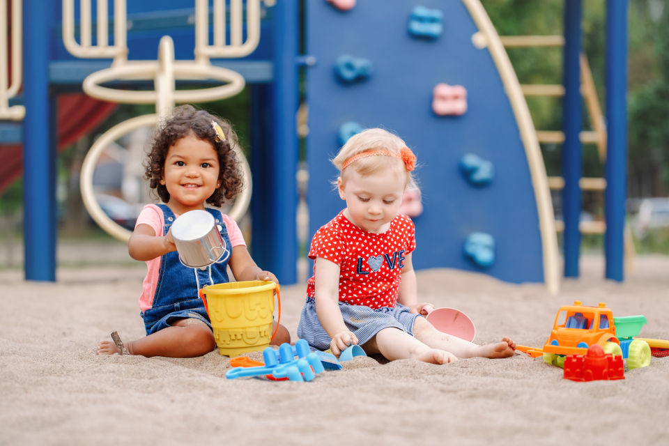 Two girls playing in sandbox