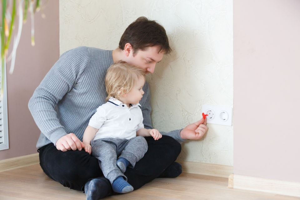 Father covering outlet while baby watches