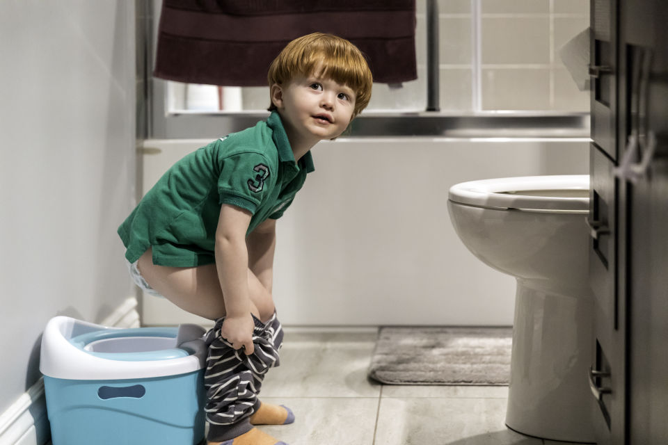 Boy wearing green shirt potty training