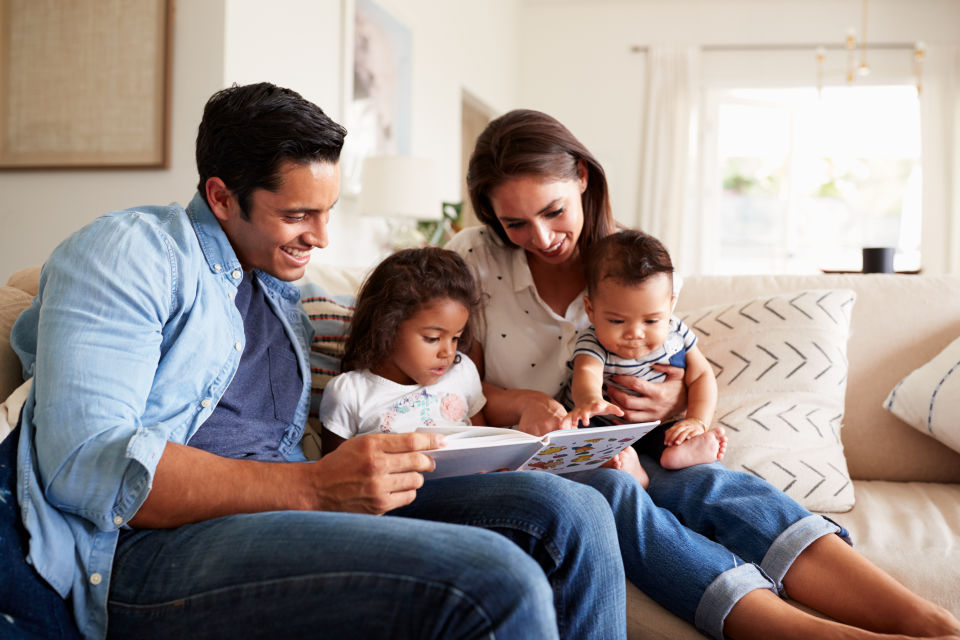 Family of four reading together on couch