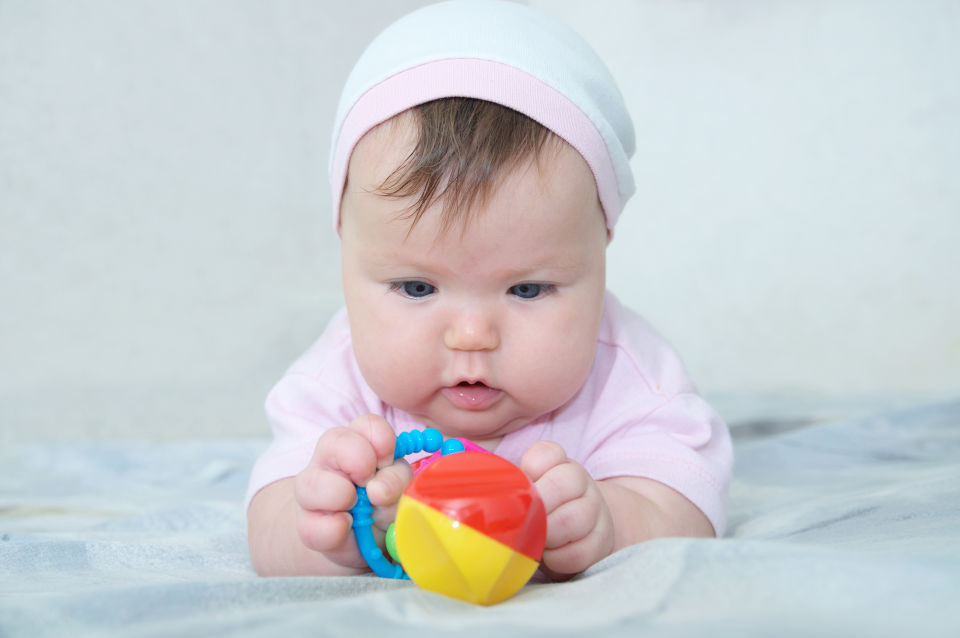 baby Girl wearing Pink Beanie Looking at Toy