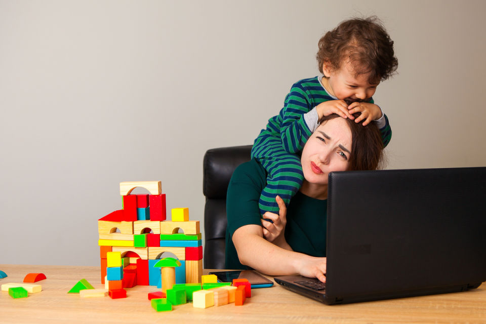 Son climbing on mothers head while she works on computer