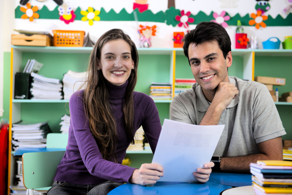 Couple in classroom female wearing purple holding paper