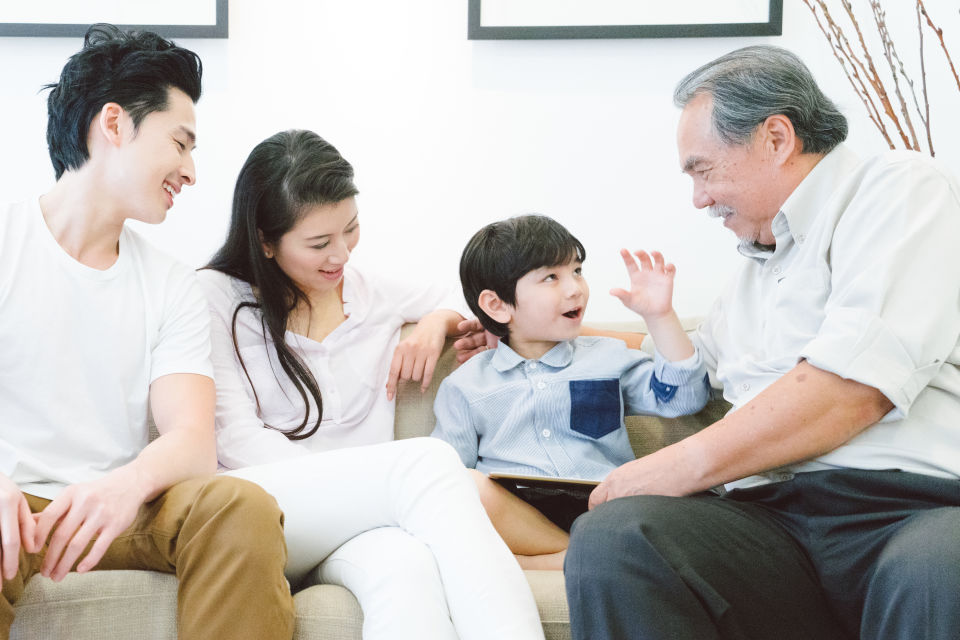 Young Parents and boy spending time with grandpa on couch