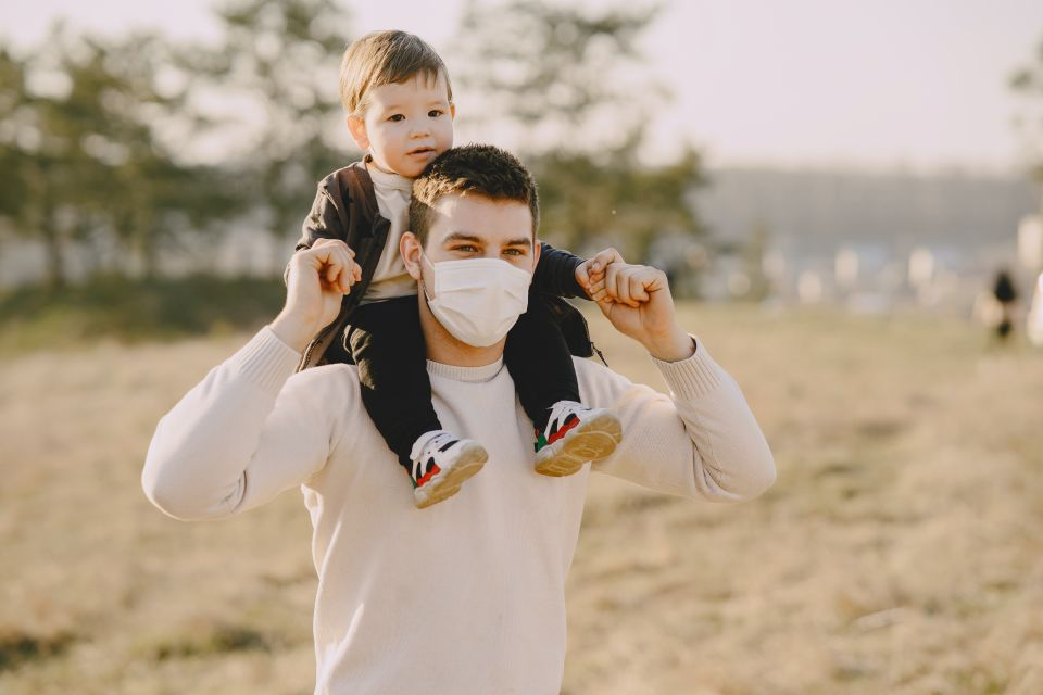 Father with face mask carrying son on shoulders