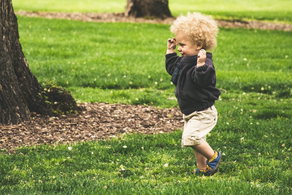 Boy with curly blonde hair running at park