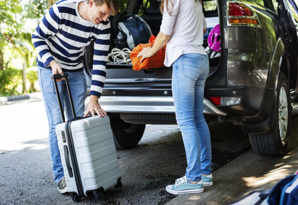Young adults loading suitcases into car