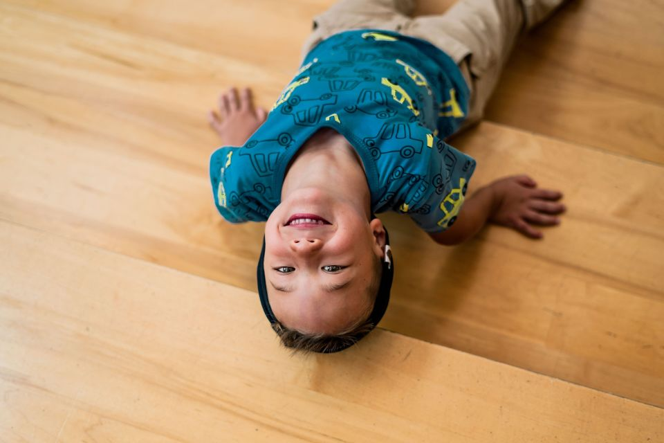 Boy laying on floor smiling at camera upside down