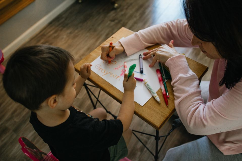 Boy drawing with teacher