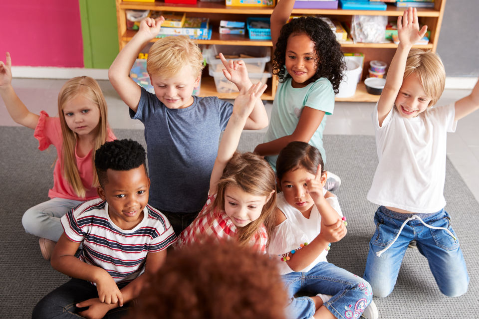 7 Students in class excited raising hands
