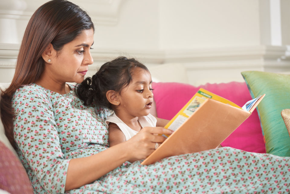 Mother and Daughter laying down reading a book on couch