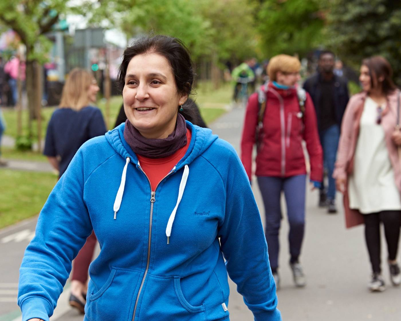 Image of a woman, walking and smiling in an open space in Greater Manchester