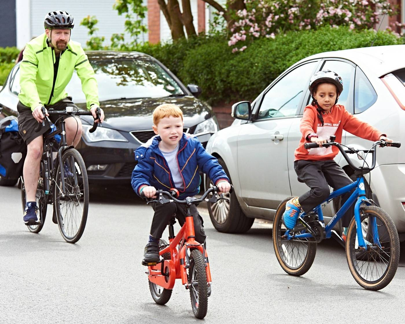 A child cycling to school with parents down a quiet road