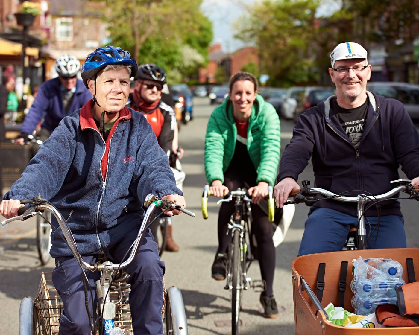 Group of smiling people riding bikes together