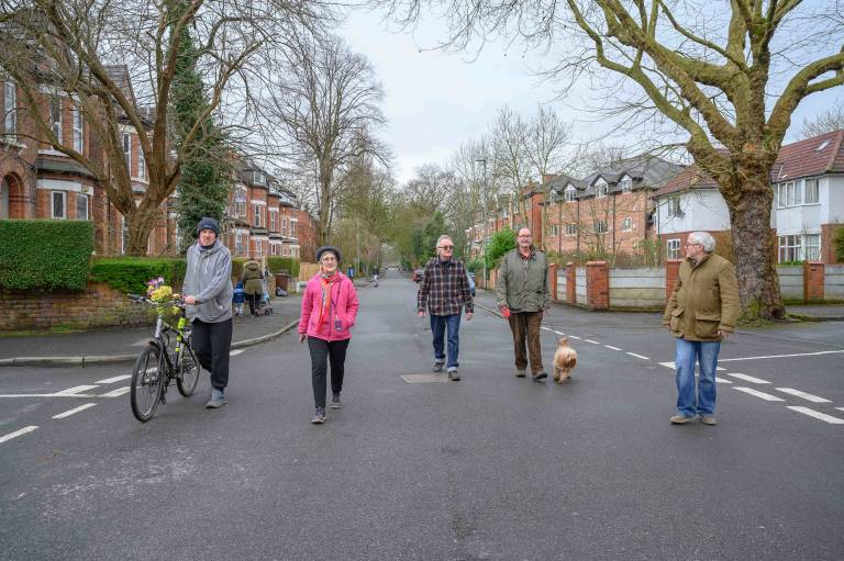 Residents of Birch in Rusholme walking down a residential street