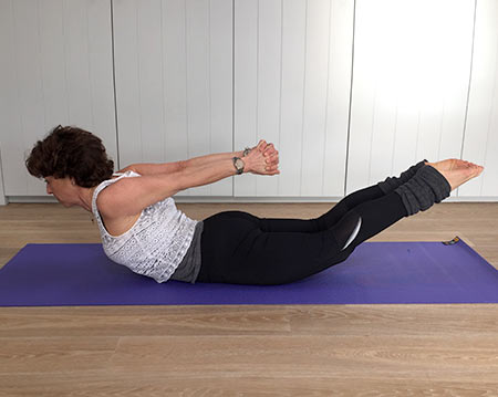 Fenella shows locust yoga pose with hands clasped behind back