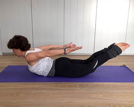 Fenella shows locust yoga pose with arms raised above body