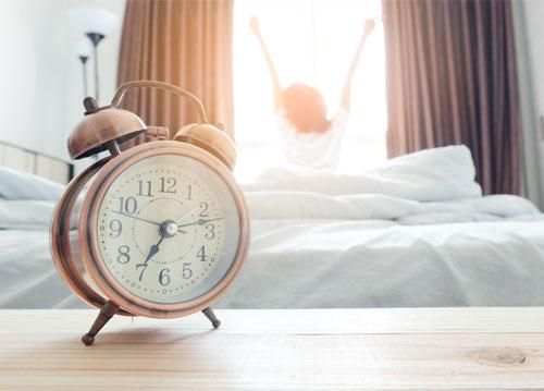 Lady waking up to alarm clock