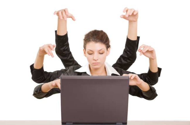 Business woman with 6 arms typing on laptop