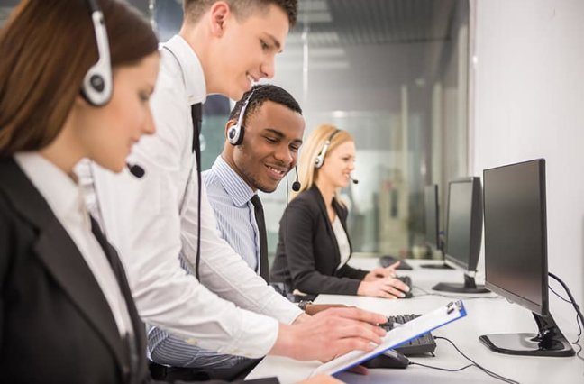 Manager explaining something to his employee in a call center.