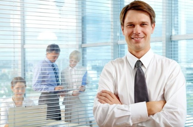 Confident businessman smiling with arms crossed