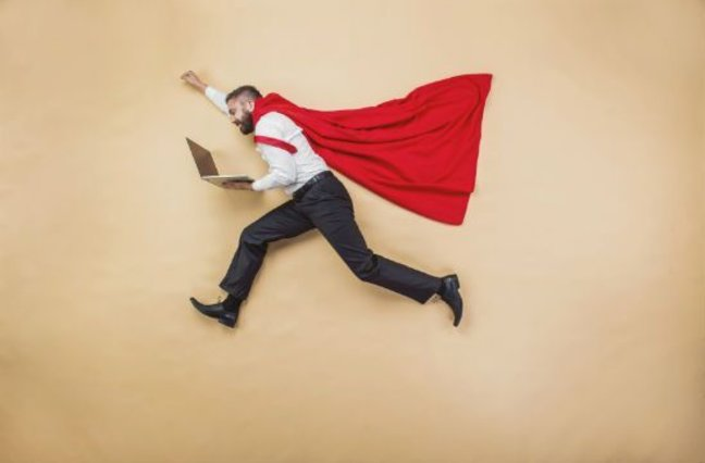 Man with red cape holding laptop