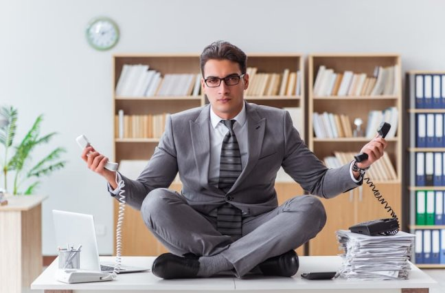 Business man sits on desk meditating with two work phones