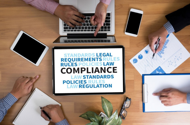 looking down on a clean desk with 3 businessmen meeting, tablet in the middle has graphic of Compliance word cloud
