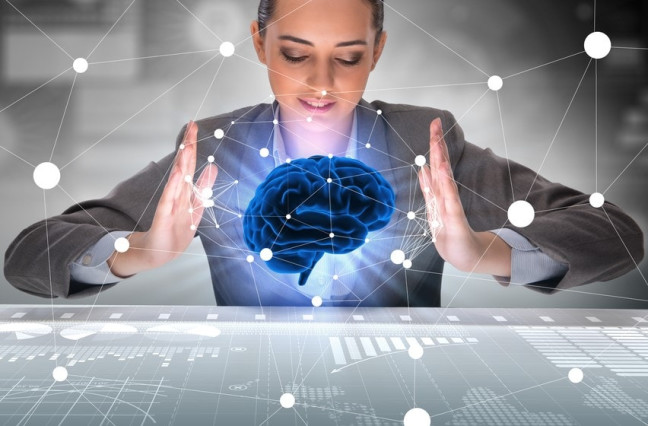 Woman holding imaginary brain above data workspace