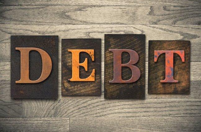Letter tiles spelling out DEBT