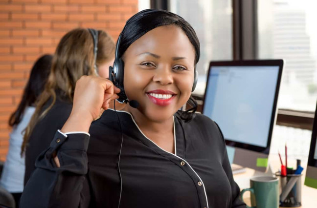 Smiling beautiful black businesswoman working in call center as a customer service agent with her multiethnic team