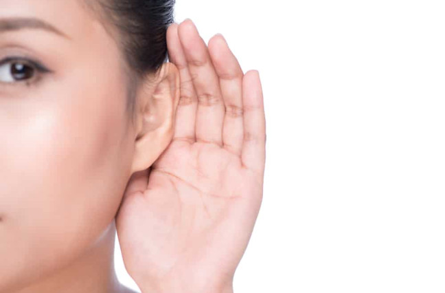 Woman cupping ear to hear better
