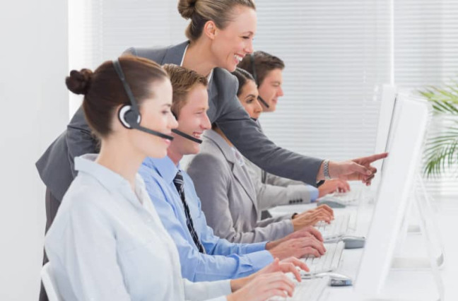 Call workers looking at their computers with a happy expression