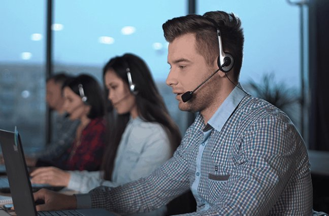 Young men in checked shirt and headset working in call center in modern worldwide office he talking and looking on screen of desktop computer