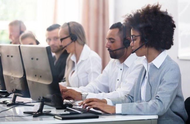 Employees with headsets sit at their desk.