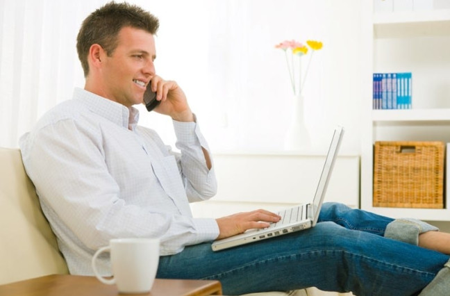 man on couch talking on phone and working on laptop