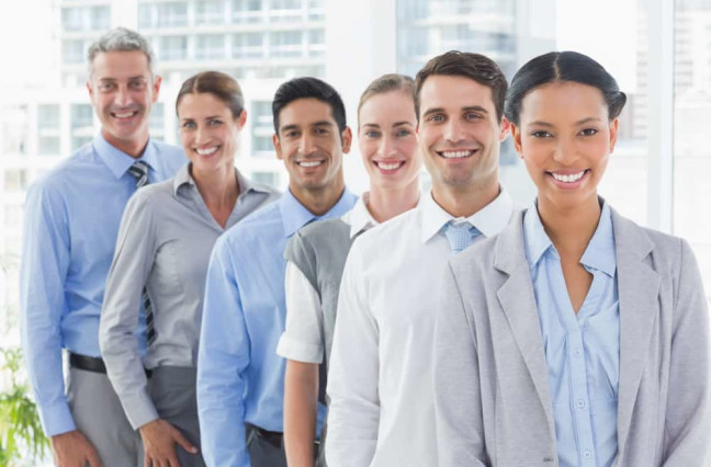 Happy business people looking at camera in a row in office
