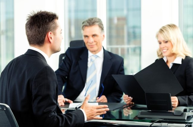 professionals interviewing man