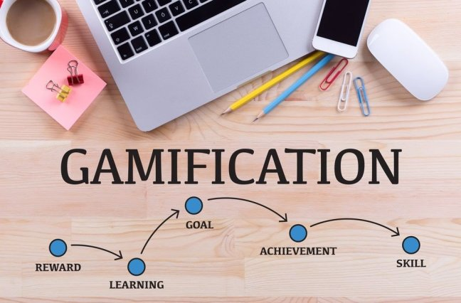 Gamification blog, looking down on a desk with laptop, pencils, phone, coffee, mouse