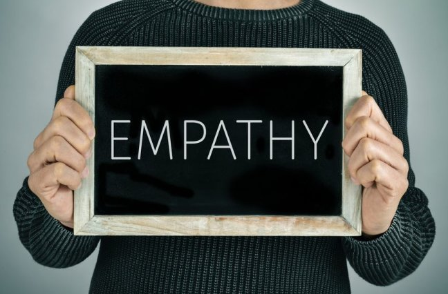 Man holding a chalkboard with the text empathy