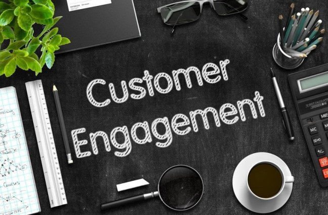 """Flatlay of desk with text saying """"Customer Engagement"""""""