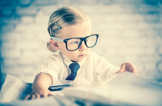 Business child with glasses sitting at blurred out messy desk
