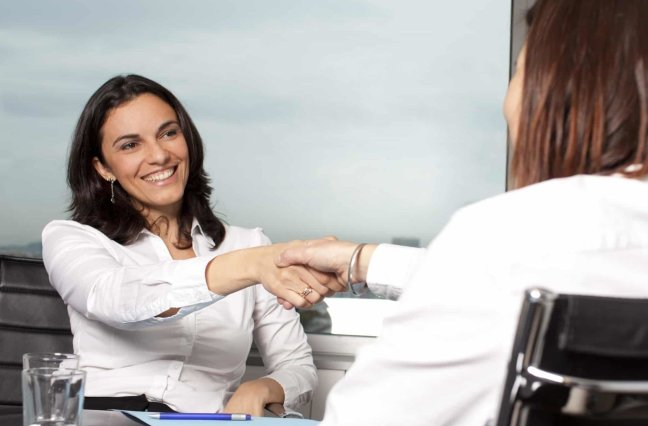 business women smiling and shaking hands