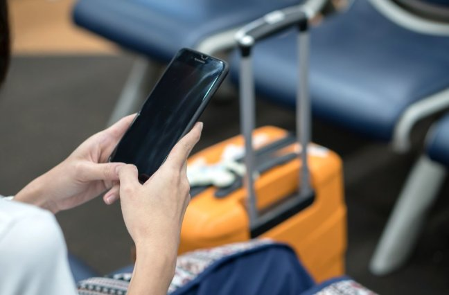 Young Asian traveler woman, using smartphone at airport
