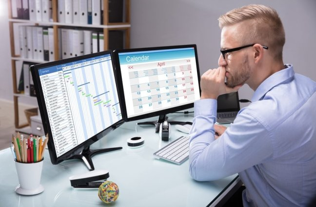 man at desk using scheduling software for call centers