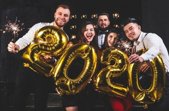 Group of people with sparklers and gold 2020 balloons.