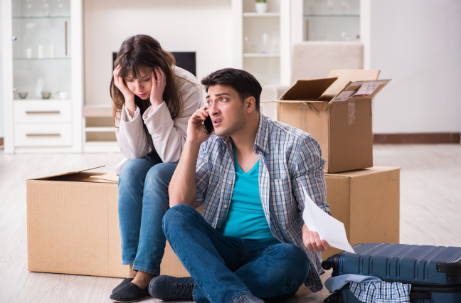 young couple receiving foreclosure notice letter, man on phone