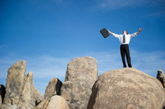 Businessman with briefcase and outstretched arms looking toward sky standing on boulders