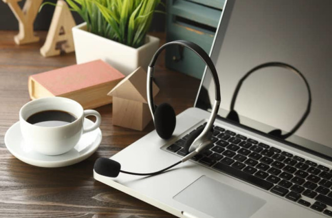 office desk with laptop, cup of coffee and headset on wooden table